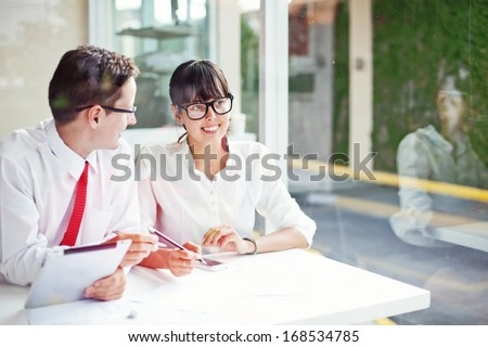 two office workers creating together (focus on face of woman) - stock photo