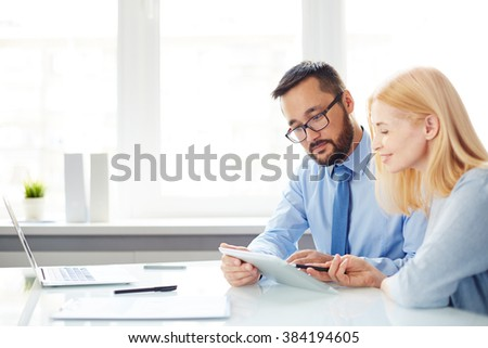 Two office workers discussing data at workplace - stock photo