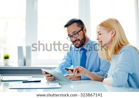 Two office workers discussing data in touchpad at meeting - stock photo