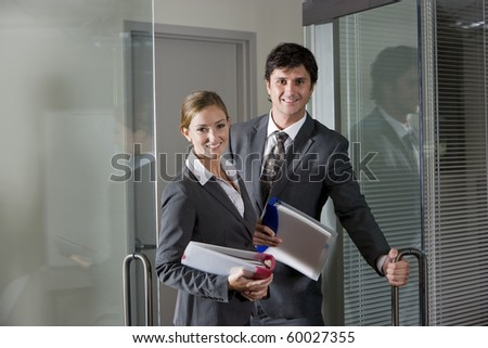 Two office workers in suits opening boardroom door - stock photo