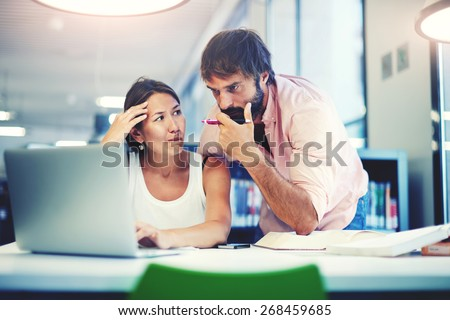 Two office workers talking in an office interior, young business colleagues discussing work on a laptop computer in co-working space, corporate business people looking at a laptop having conversation - stock photo