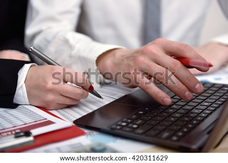 Two office workers working together on project, gesturing and looking at laptop screen