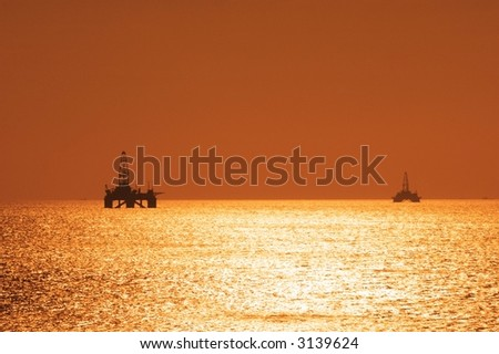 Two offshore oil rigs during sunset  in Caspian sea - stock photo