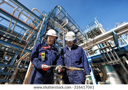 two oil and gas workers with main station at refinery industry - stock photo
