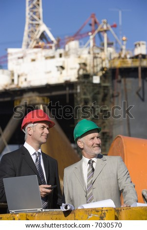 Two oil platform inspectors with a laptop, with the platform in the background - stock photo