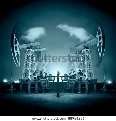 Two oil pump-jack in action. Night view. Long exposure. Toned. - stock photo