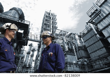 two oil workers, engineers talking to each other, oil and gas refinery in background - stock photo