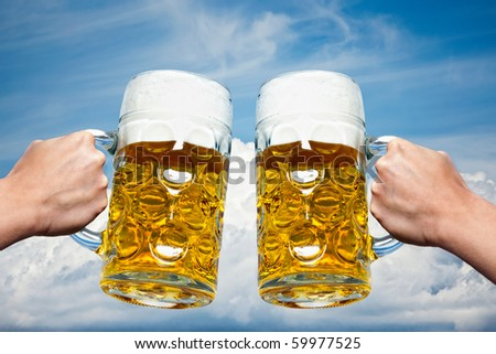 Two Oktoberfest beers on a Bavarian blue sky background and white clouds. - stock photo