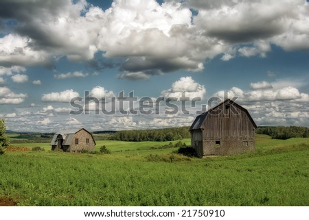 Two old barns in a field with beautiful clouds - stock photo