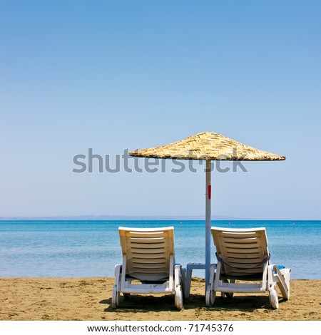 Two old beach chairs and umbrella - stock photo