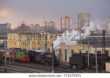 Two old black diesel locomotives in the railway depot against the background of the city and one new green locomotive From the pipe smoke is coming.