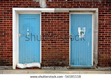 Two old blue wooden doors set into red brick wall in seaside town of Weymouth - stock photo