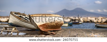 Two old boats on a bank by the sea with a big volcano mountain in the background - stock photo