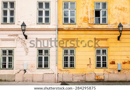 Two old buildings of yellow and beige colors, facade - stock photo