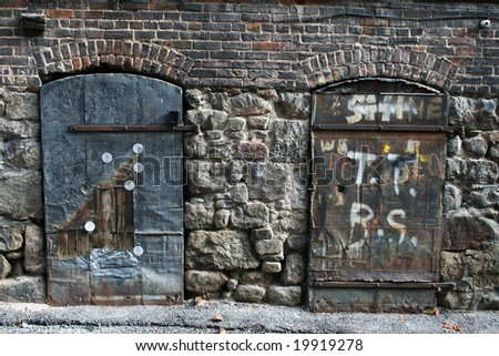 Two Old Doors against a Stone and brick wall in Butte, Montana. - stock photo