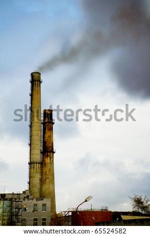 Two old factory smokestack tube against the cloudy sky - stock photo