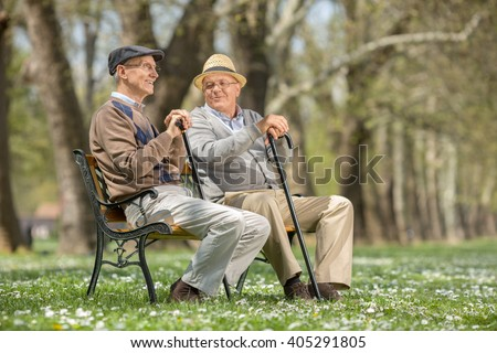 Two old friends sitting on a wooden bench in park and talking to each other - stock photo