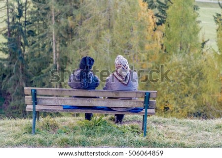 two old ladies sitting on a wooden bench looking the view of the mountains in the Dolomites in autumn