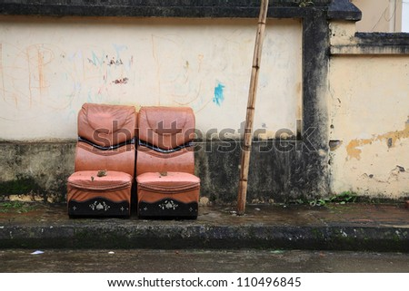 Two old leather chairs near grungy wall on the footpath - stock photo