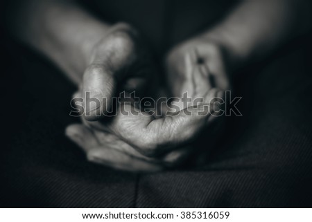 Two old man's hands on a dark background