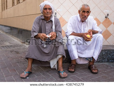 Two old men after ablution procedure sitting in front of the mosque. Dubai, UAE - 16/JUL/2016
