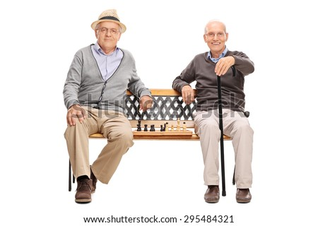 Two old men posing seated on a wooden bench with a chessboard between them isolated on white background - stock photo