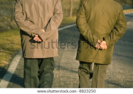 Two old men walking in park while holding their hands on back - stock photo