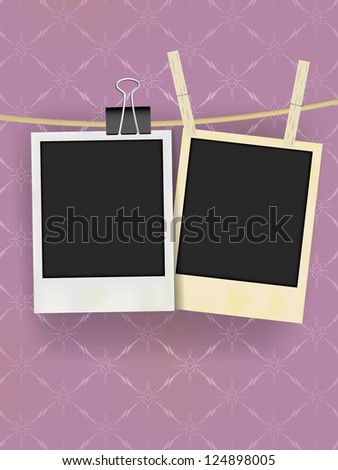 Two Old Retro Blank Photo Frames Hanging on Rope - on Vintage Wallpaper - stock photo