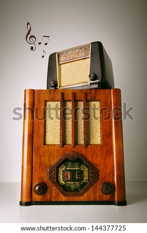 Two old retro revival radios on top of another with music notes - stock photo