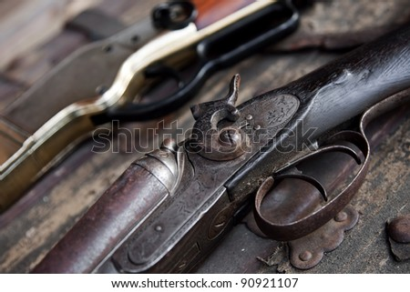 Two old rifles sit on a table - stock photo