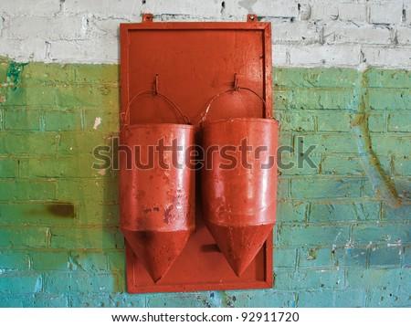 Two old, rusty fire buckets hanging on a wall - stock photo