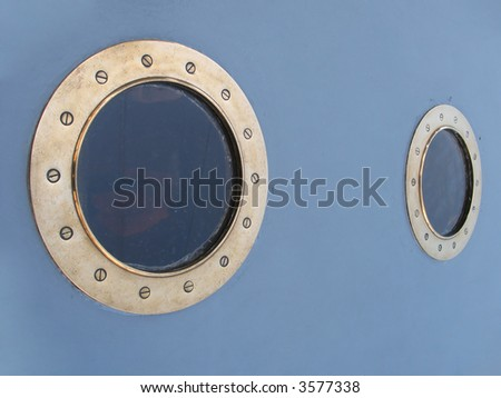 Two old ship windows on a dark blue wall - stock photo