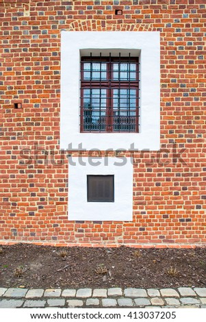 Two old square windows, one with steel grating. Old red brick wall. - stock photo