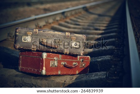 Two old suitcases lie on railway rails. - stock photo