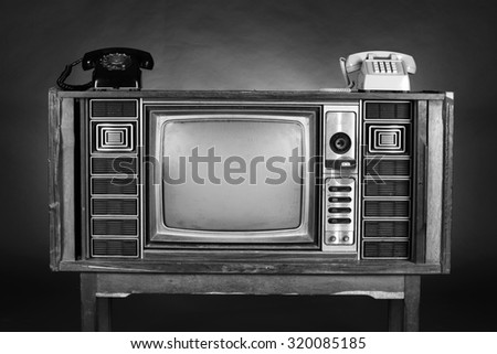 Two Old  telephone put on an vintage television on brown background. - stock photo