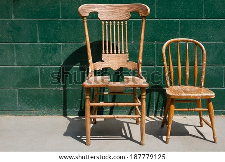 Two old weathered and broken wooden chairs for an adult and a child against a green brick wall. - stock photo
