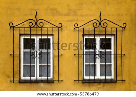 Two old windows with ornamented metal lattice - stock photo