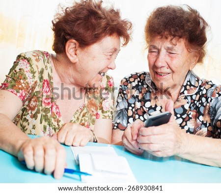Two old women consider receipts. Female counts bill - stock photo