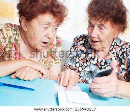 Two old women consider receipts. Surprised Female counts bill - stock photo