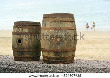 Two old wooden barrels for distilled beverage at a flea market in the background two youths walking on the Beach in Brittany, France. - stock photo