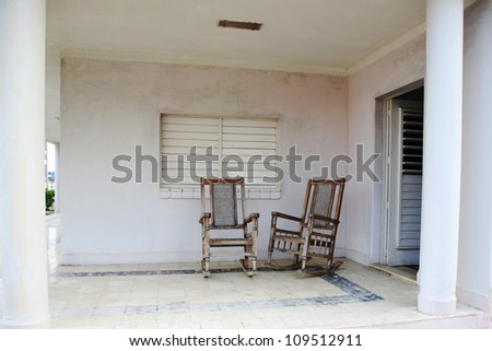 Two old wooden chairs on the porch in Cuba - stock photo