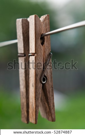 Two old wooden clothes pegs on the Wire - stock photo
