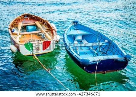Two old wooden fishing boats in turquoise water. Italy. - stock photo