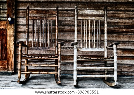 Two old wooden rocking chairs on front porch, part of door and the house's wooden shingles can be seen. - stock photo