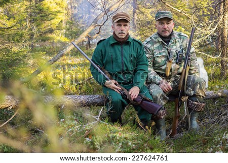 Two older hunters rest, sitting on a log - stock photo