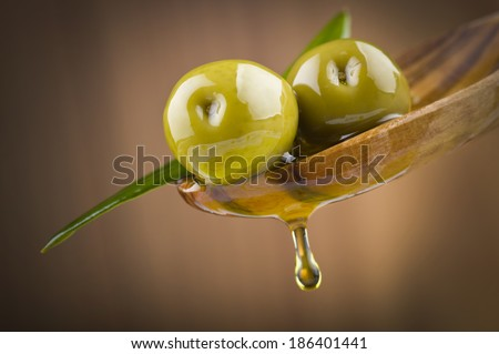 Two olives and leaves with drop oil on wood spoon  - stock photo