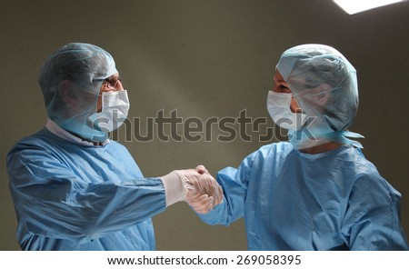 Two OP doctors shaking hands after successful work - stock photo