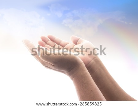 Two open empty hands with palms up, over blurred world map of clouds background. - stock photo