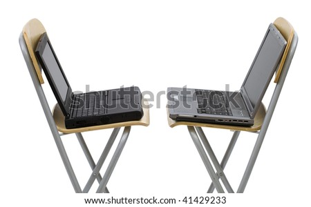 two open laptops standing on bar high chairs turned in one's side. White background. - stock photo
