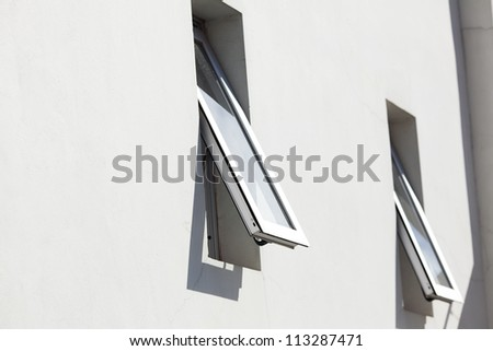 two open windows on the background of the house - stock photo